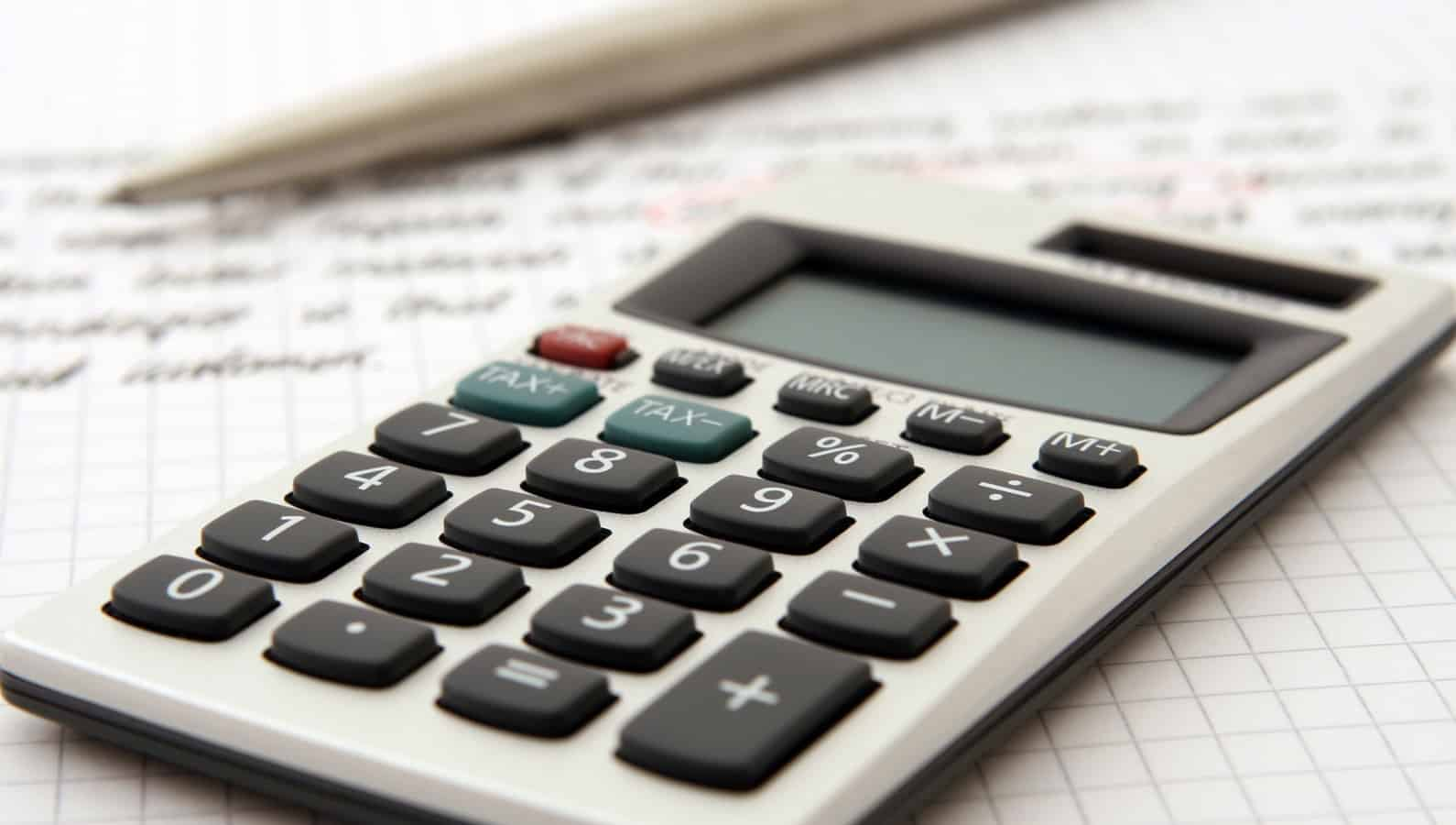 calculator on notebook with pen for calculating investment