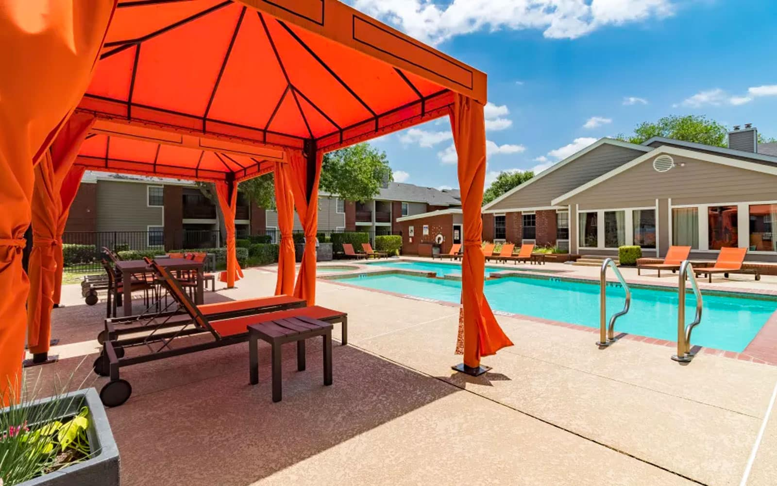Orange gazebo with chairs in front of pool at multifamily complex